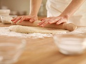 Woman pressing dough with rolling pin