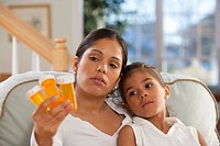 Hispanic woman sitting with her daughter and holding pill bottles