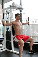 fit male exercising in gym with out a shirt on showing a very ripped muscular body.