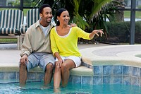 A happy African American man and woman couple in their thirties sitting outside by a pool smiling and pointing
