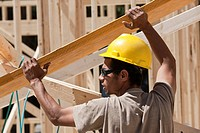Carpenter lifting a laminated beam at a construction site