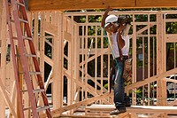 Carpenter standing at a construction site holding a nail gun