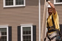 Carpenter carrying a particle board