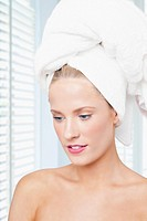 Caucasian woman with hair wrapped in towel