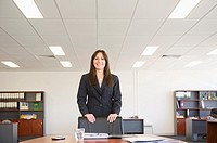 Hispanic businesswoman standing in office