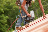 Hispanic carpenter using a nail gun on roof panels