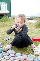 Girl colouring stones, Flatey, Iceland, Scandinavia, Northern Europe, Europe