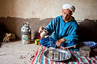 Elderly Berber man wearing a turban sitting on the floor on a rug pouring traditional mint tea from a silver jug, Kelaa M'gouna, High Atlas Mountains,...