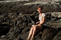 Woman sitting on the beach near Marine iguanas Amblyrhynchus cristatus, Punta Espinoza, Fernandina Island, Galapagos Islands, Ecuador