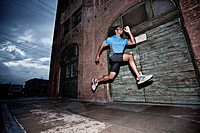Male athlete running on sidewalk