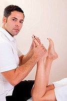 Therapist doing foot massage. Spa studio shot