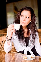 Beautiful brunette girl having a coffee.