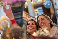 Woman looking at Christmas decorations at a store with her daughter