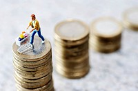 Miniature figurines of a man with a shopping cart on a coin stack, symbolic image for rising food prices