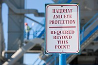 Warning sign saying Hardhat and Eye Protection Required Beyond This Point at an industrial plant