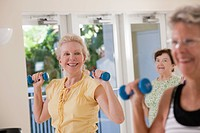 Women exercising with dumbbells in a health club
