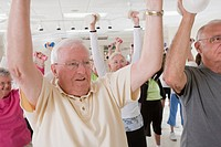 People exercising with dumbbells in a health club
