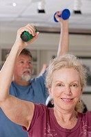 Man and woman exercising with dumbbells in a health club