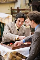Two businessmen playing backgammon