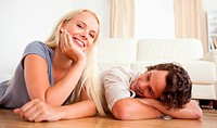 Lovely couple lying on the floor in their living room