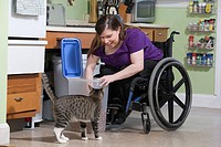Woman with Spina Bifida in a wheelchair feeding a cat in the accessible kitchen