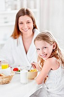 Mother and daughter eating breakfast in the kitchen