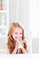 Beautiful little girl drinking milk in the kitchen