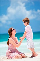 Happy mother and son at tropical beach