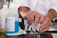 Scientist picking up sample bottles and reagent vials in the laboratory of water treatment plant
