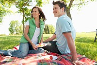 Attractive young man and woman smile while having a picnic.