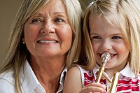 Young girl sits on her grandmother´s lap and plays a trumpet.
