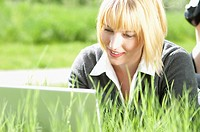 Businesswoman works on a laptop while lying in the grass.