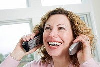 View of a cheerful mature woman using a cordless and a mobile phone