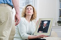 Woman showing picture of her son working in the military
