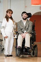 Portrait of handicapped woman standing by handicapped man on wheelchair