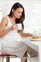 Woman reads the newspaper over coffee and breakfast.