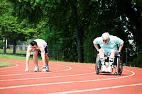 Young man racing with a handicapped senior man on a racetrack