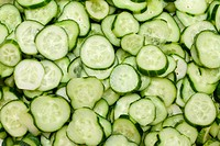 Much cut fresh cucumbers put by background