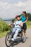Young man riding adaptive bike with a young woman standing behind him and smiling