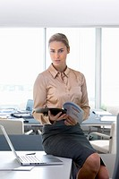 Portrait of confident businesswoman holding report in office