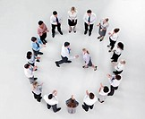 Businessman and businesswoman shaking hands in circle formed by clapping co_workers