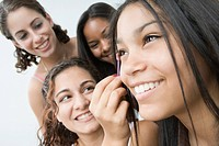 Close_up of a teenage girl applying mascara on her eye with her friends smiling beside her
