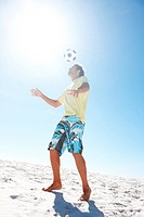 Image of handsome young boy playing football at the beach