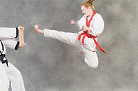Young woman practicing karate with her karate instructor