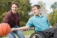 Young man sitting in a wheelchair and playing basketball with his father