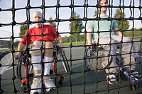 Two handicapped men sitting in wheelchair viewed through a tennis net