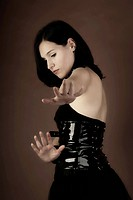 Woman, Gothic look, wearing a patent leather dress, hands reaching out