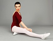 Beautiful woman sitting in leotard on a gray background.