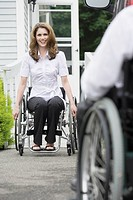 Mid adult woman sitting in a wheelchair and smiling