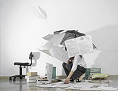 Woman indoors under an umbrella picks up paperwork while more falls down on her.